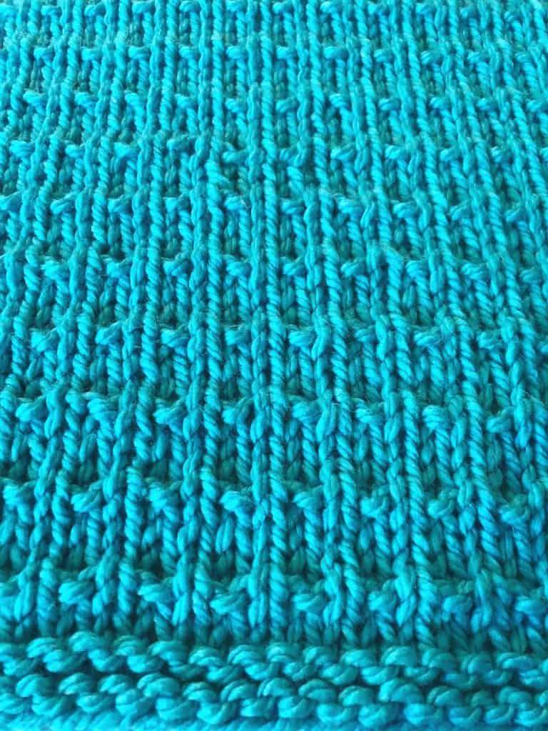 Stitch up close in blue chunky yarn blanket.