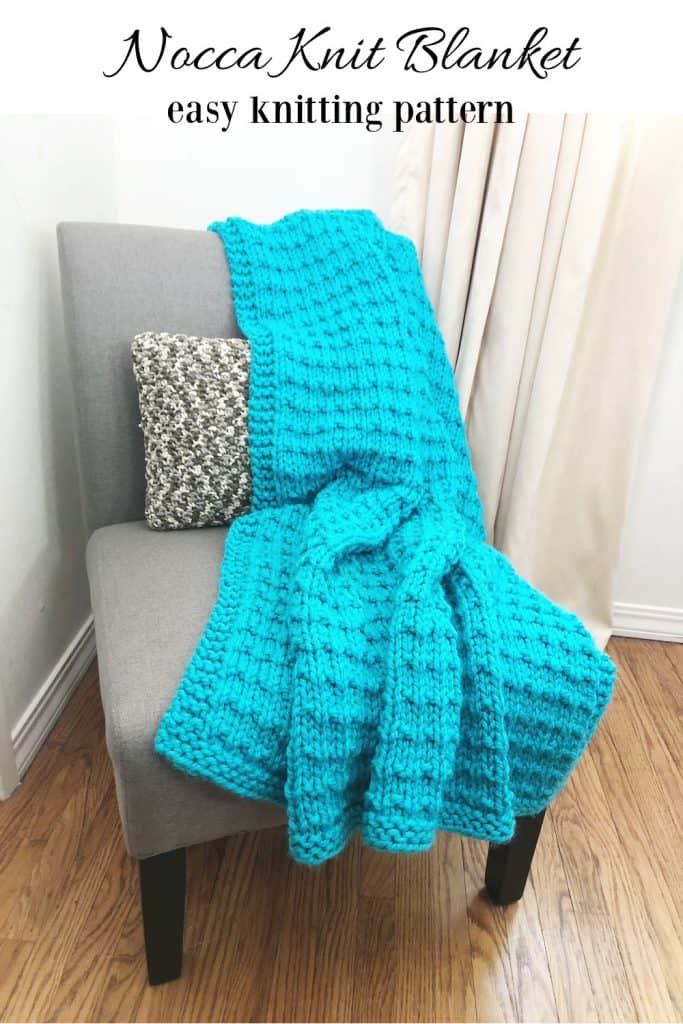 Chunky blue knit blanket on grey chair.