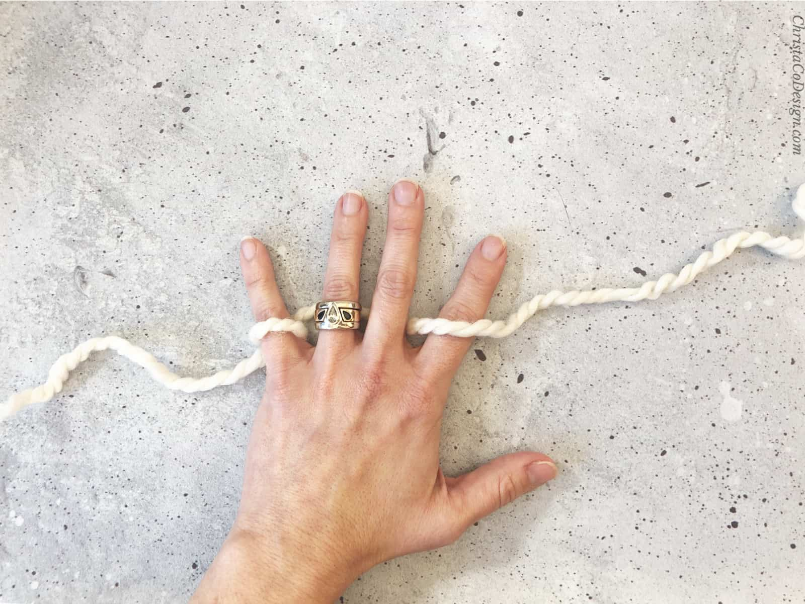 picture of yarn threaded through fingers for crochet
