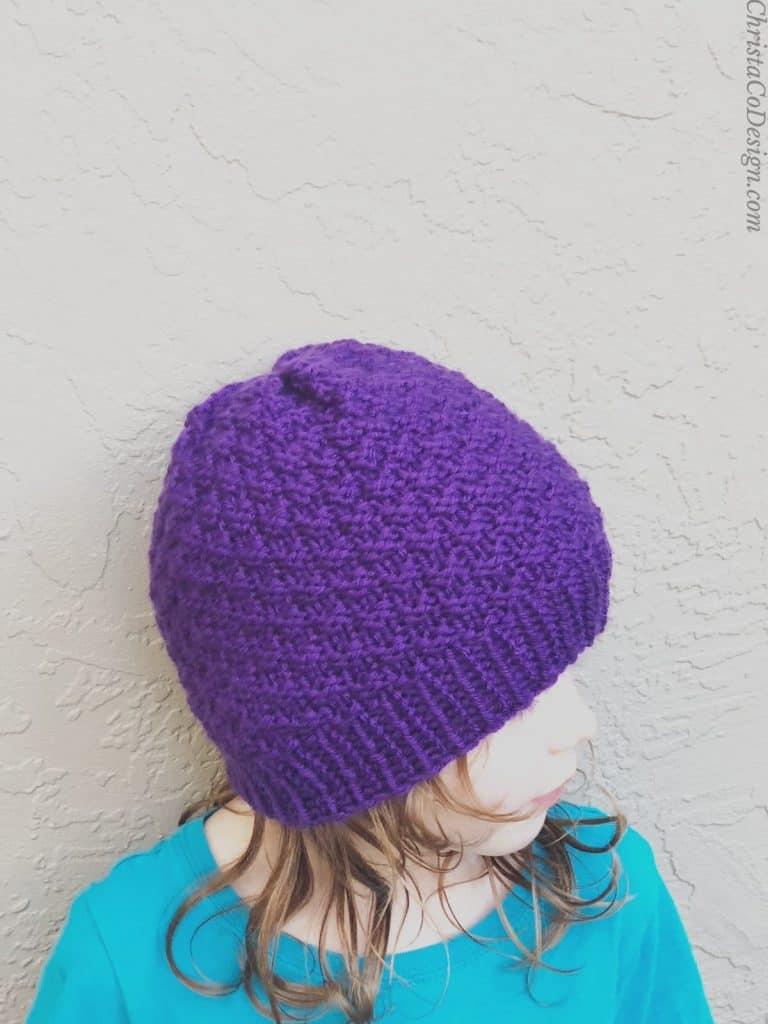 A girl in a purple knit hat.