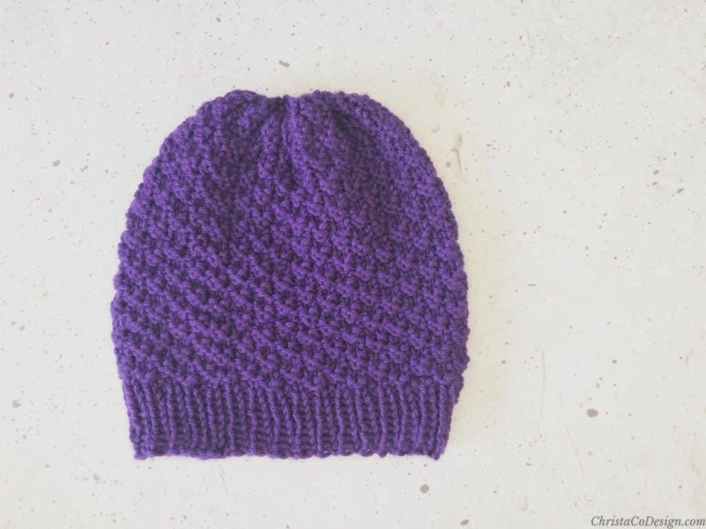 Purple knit beanie laid flat.