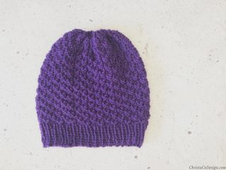 Purple knit beanie laid flat.