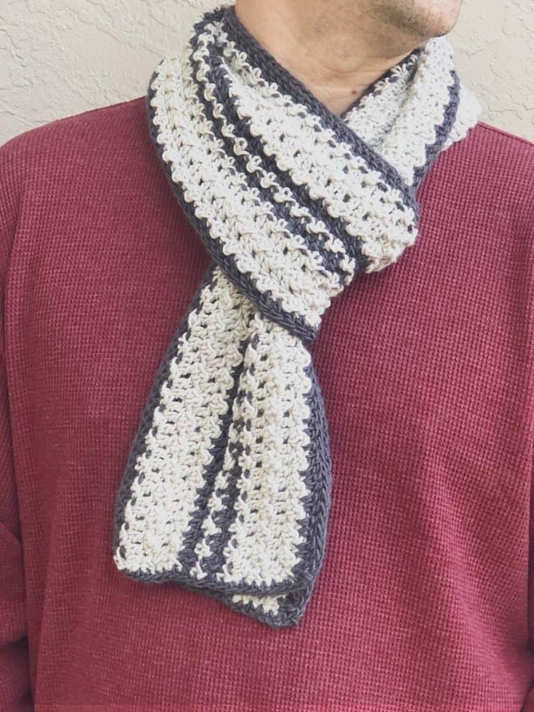 Grey striped textured crochet scarf pattern looped on mans neck against burgundy shirt.