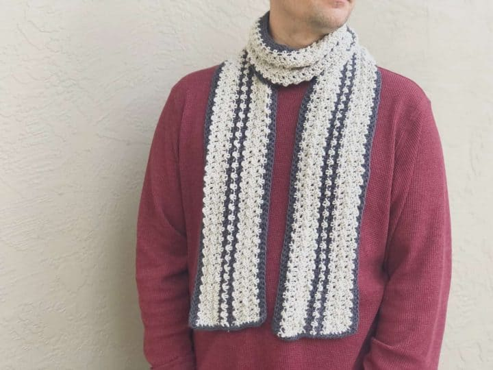 Man in burgundy sweater with striped grey and charcoal crochet scarf on.