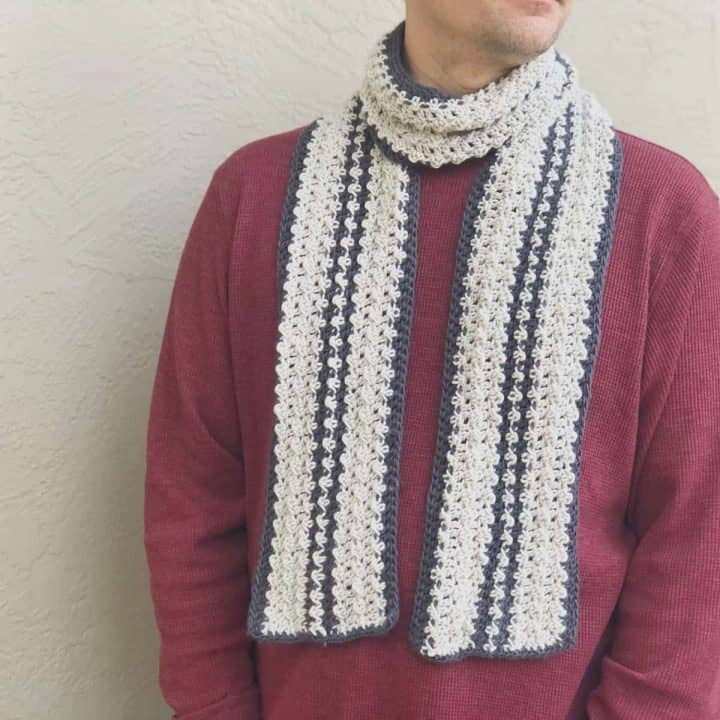 picture of man in burgundy sweater with striped grey and charcoal crochet scarf on