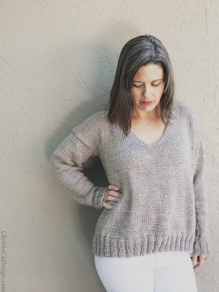 Woman looks down while wearing knit v-neck pullover.