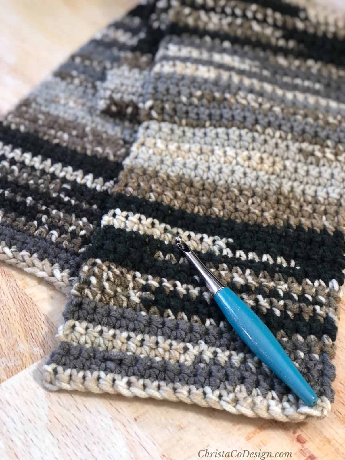 Black, grey and beige striped scarf with hook.