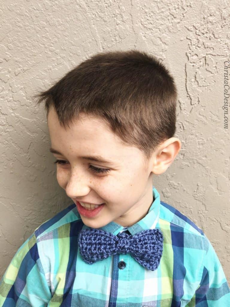 Boy in blue crochet bowtie and plaid shirt.