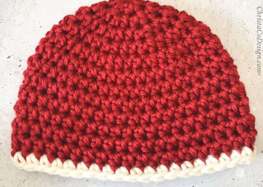 Red crochet beanie with white trim.