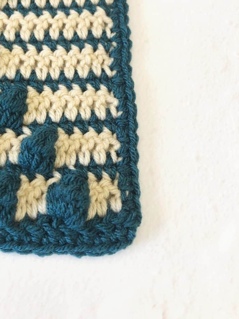 Crochet square with blue and beige color changes.