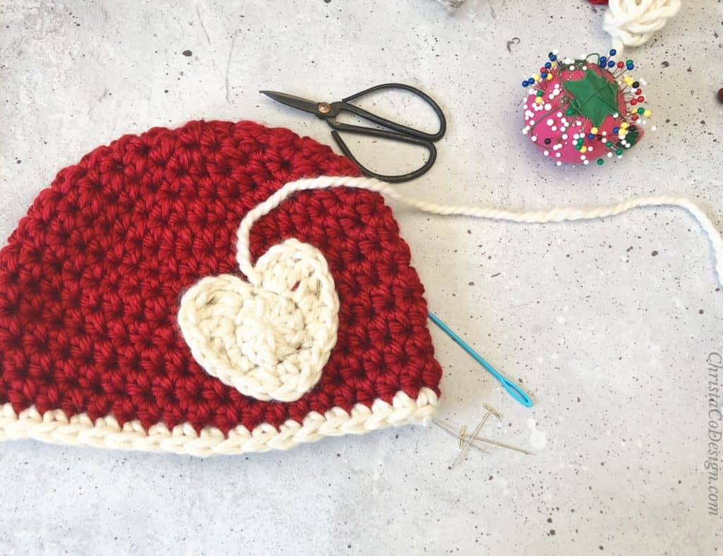 Red hat with white crochet heart and sewing supplies.