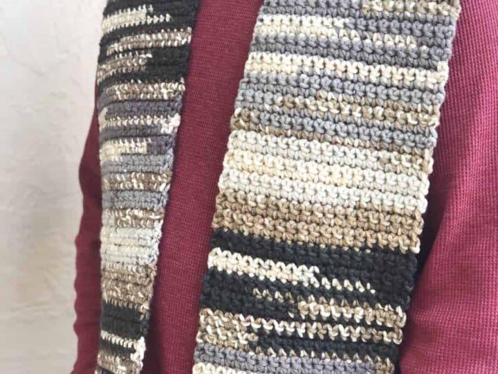 Man wearing black, grey, beige striped crochet scarf for beginners.
