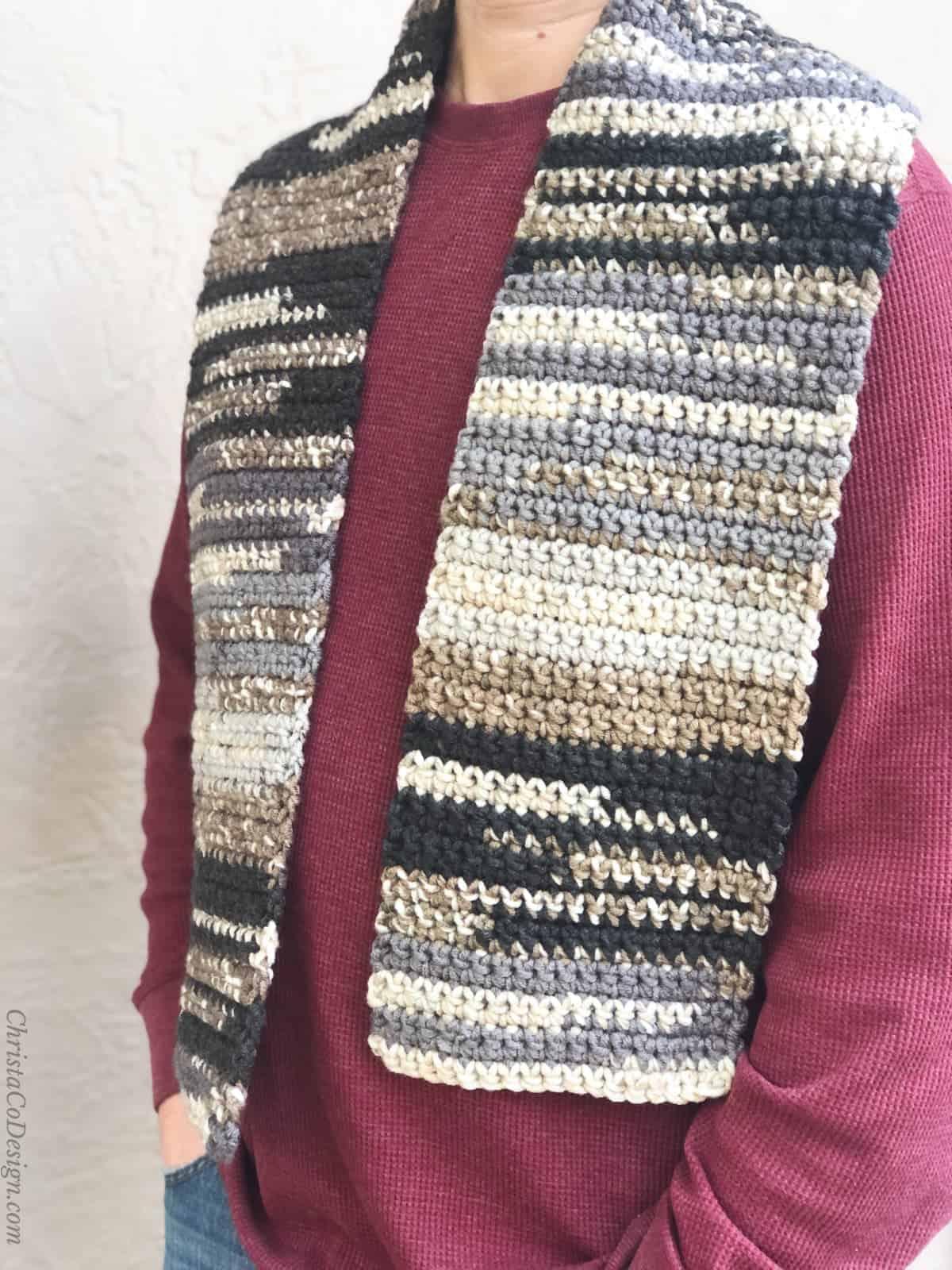 Man wearing black, grey, beige striped scarf.
