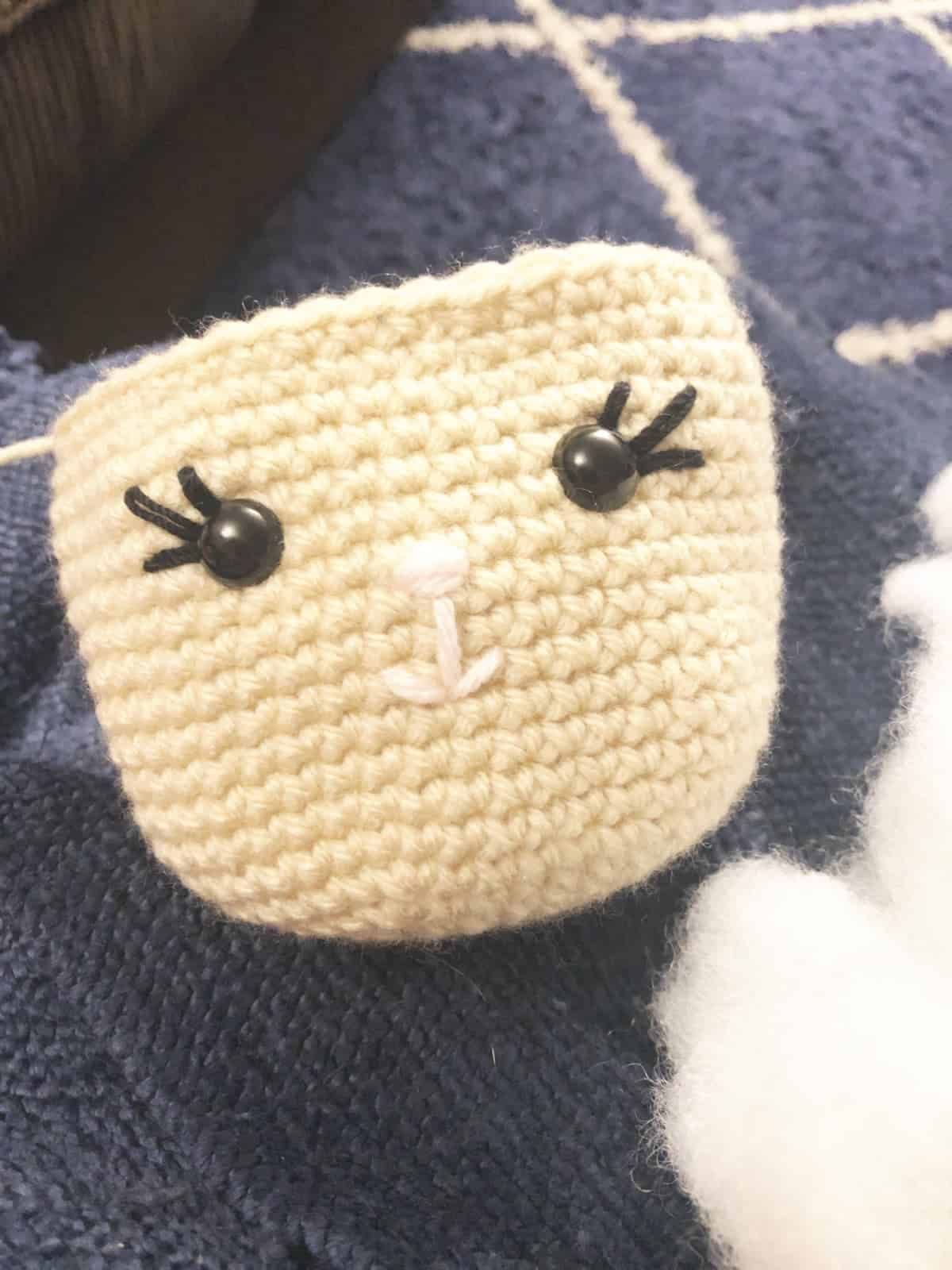 Close up of crochet face embroidery.