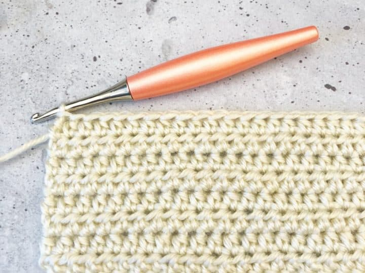 A swatch of hdc stitches in white Wander Acrylic yarn with peach odyssey hook.