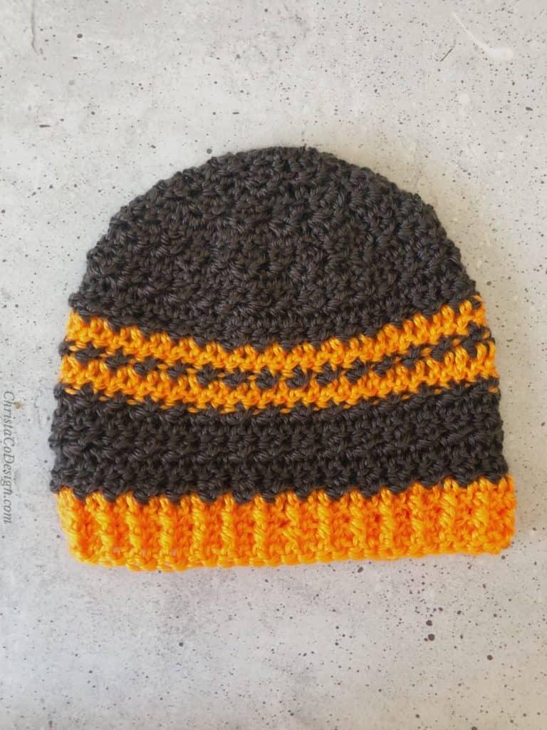 Dark grey beanie with two center stripes in orange.