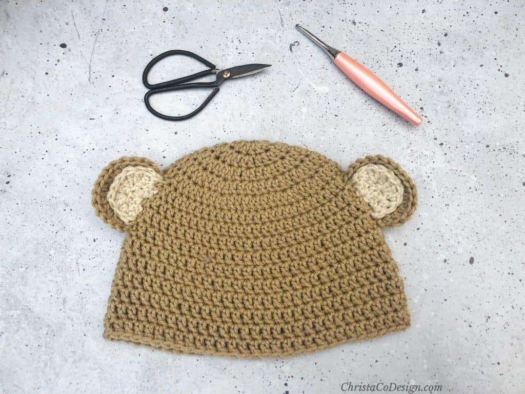 Light brown bear hat with scissors and hook.