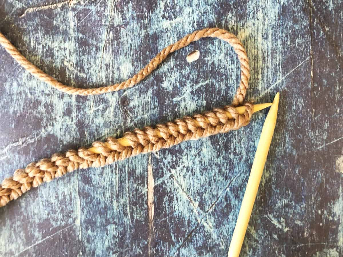 Brown stitches cast on needles.