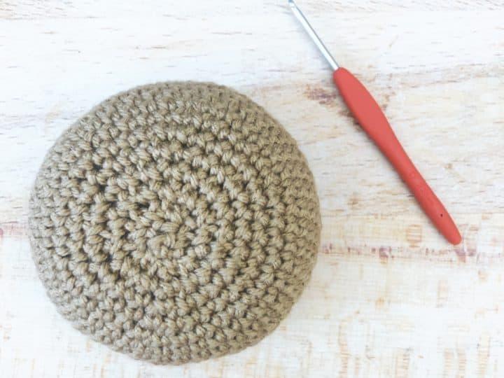 Crochet ball in tan yarn with hook.