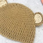Crochet bear ear hat with scissors and hooks.