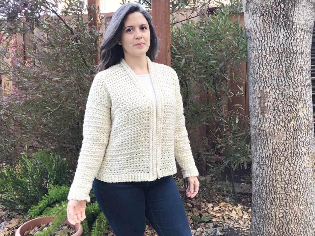 Woman in white crochet cardigan pattern outside.
