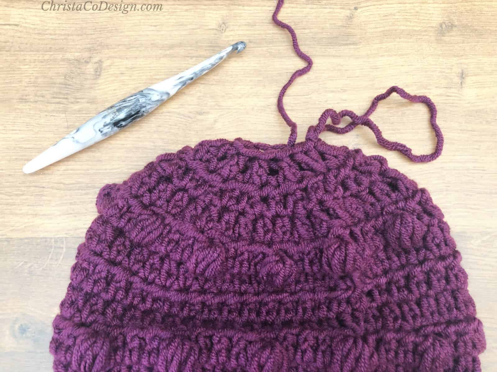 Close top of hat with yarn tail.