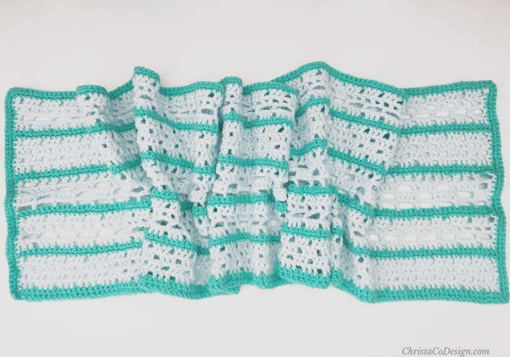 Rectangle wrap in blue and green crochet lace blocks.