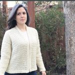 Woman in crochet cardigan outside.