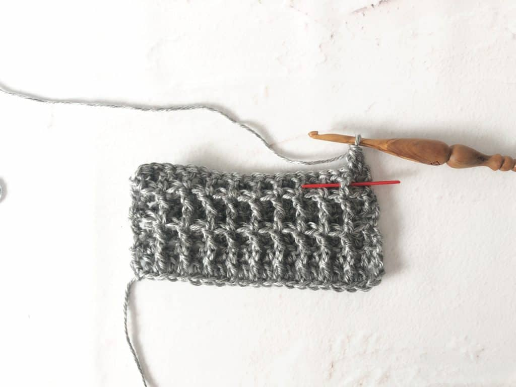 Red needle inserted to show post of crochet stitch.