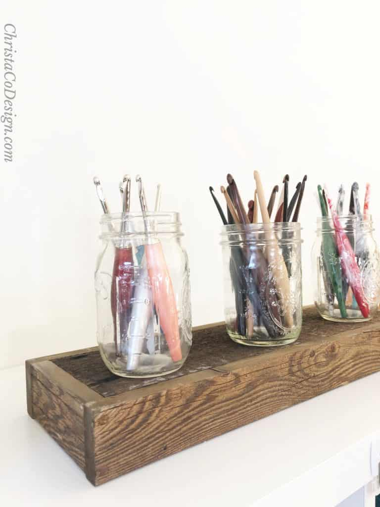 Variety of crochet needles sizes and hooks displayed in mason jars.