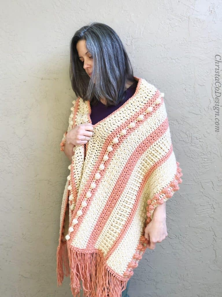 Woman with texture orange and cream shawl on.