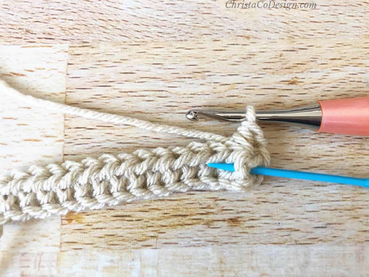 Blue needle under post of stitch.