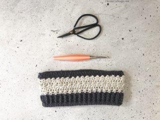 Flat lay of scissors, peach hook and striped ear warmer.