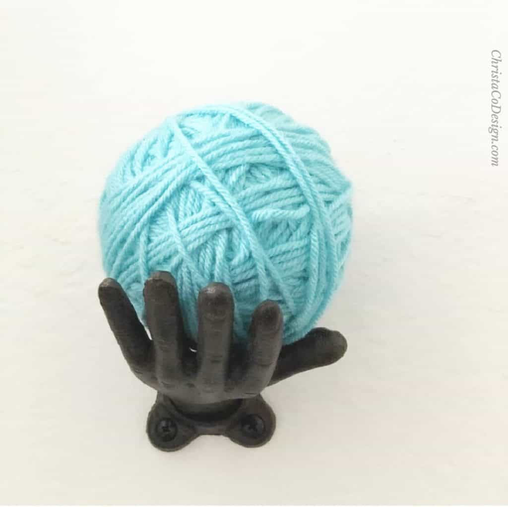 Blue ball of yarn on hand shaped hook.