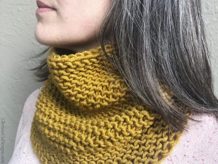 Woman with honey yellow cowl knit in garter on neck.
