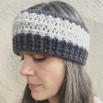 Woman in dark grey and light striped crochet earwarmer.