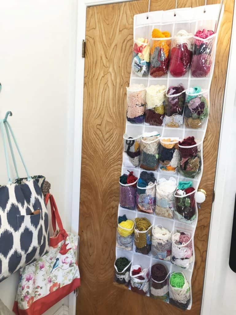 Over door shoe storage filled with yarn.