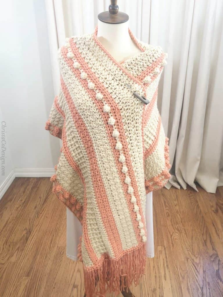 Fringed shawl draped over mannequin.