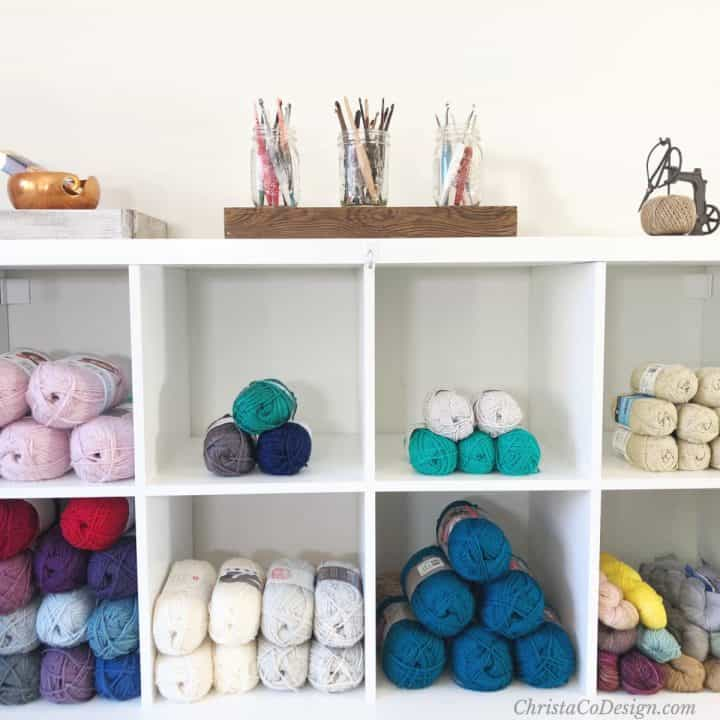 Shelf with yarn and hooks on top in jars.
