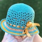 Toddler in teal crochet sun hat with brim.