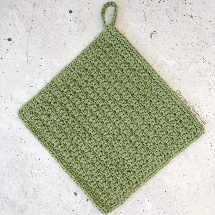 Crochet dishcloth in green with loop.