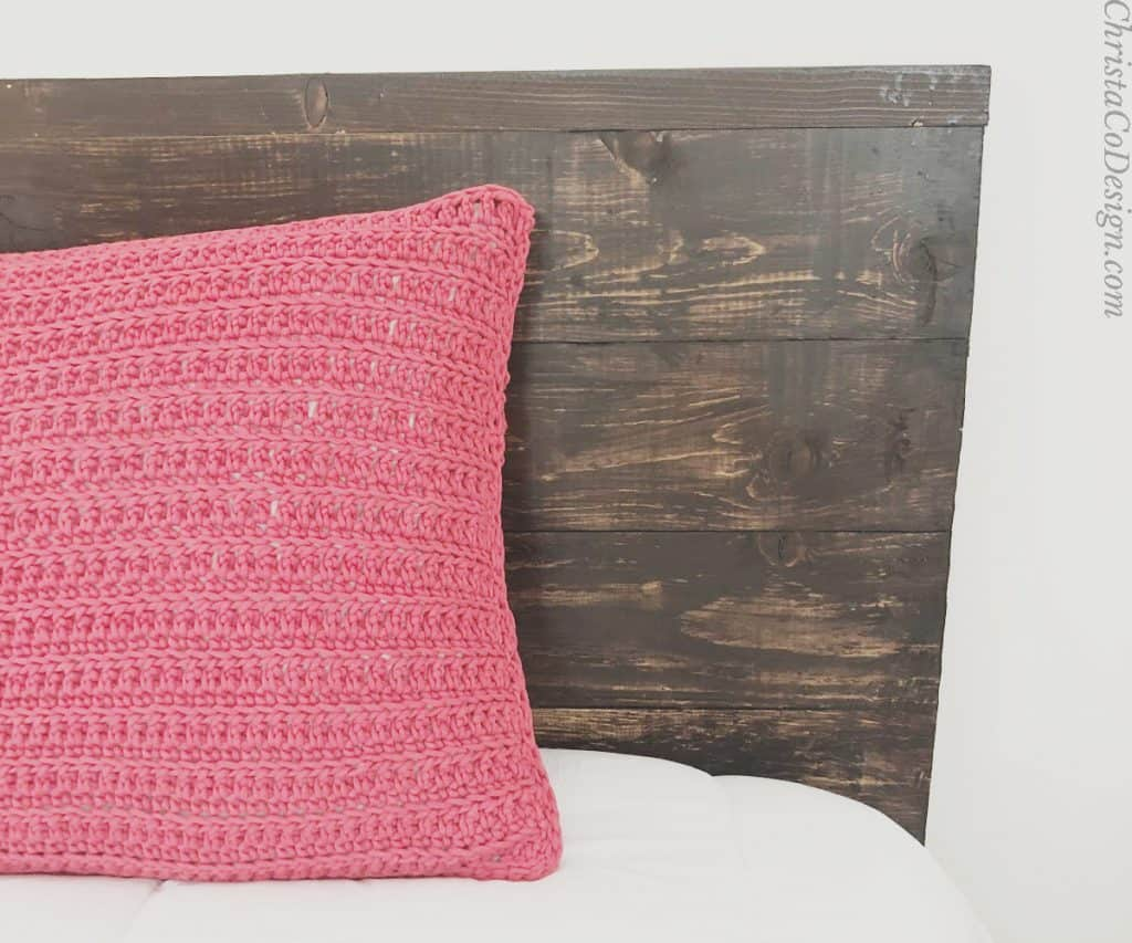 Red crochet pillow on bed.