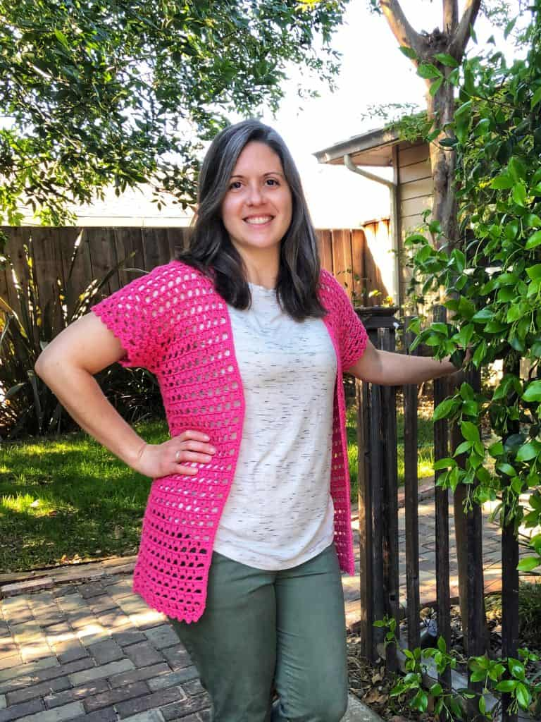Woman smiling in pink crochet summer cardigan free pattern.