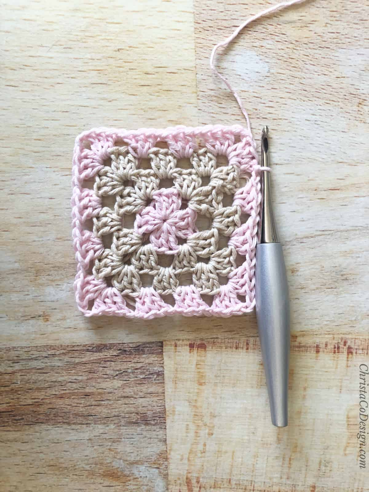 Four rounds of granny square in pink and beige.
