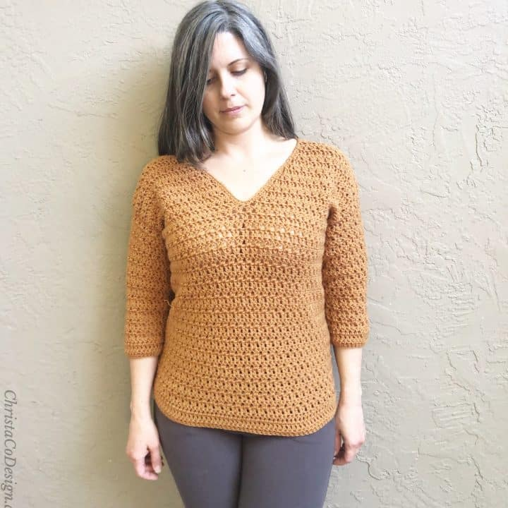 Woman in v-neck crochet sweater camel color.