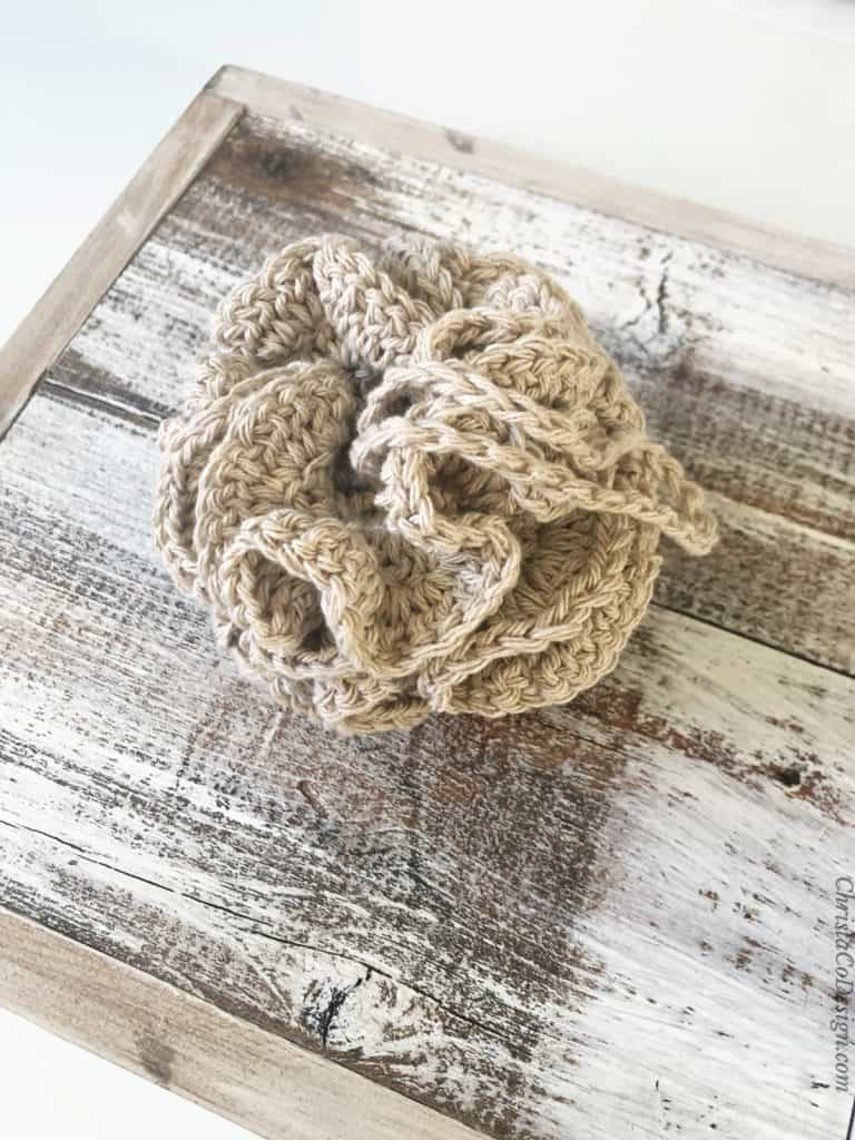 Crochet loofa in beige cotton yarn.