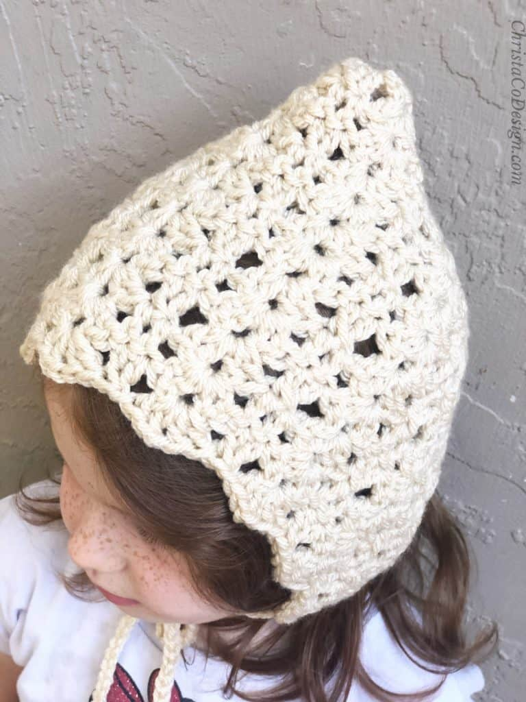 Girl looking to the side in vintage crochet bonnet pattern in cream color.