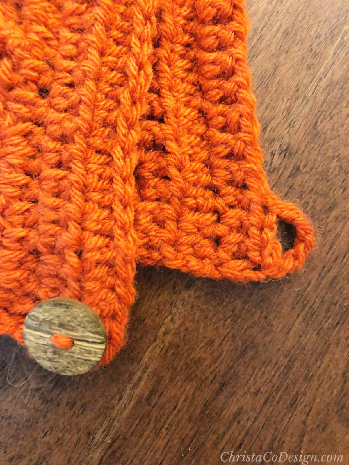 Rust bonnet with button and buttonhole.