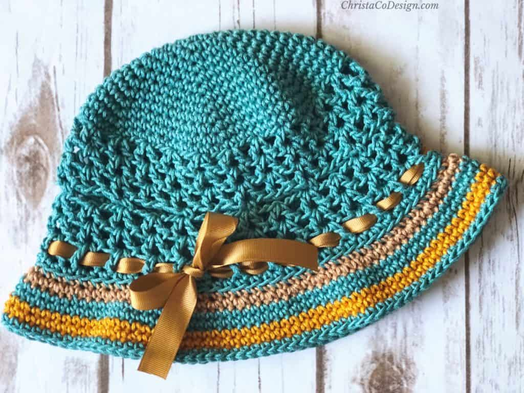 Teal and gold brimmed sun hat laid flat.
