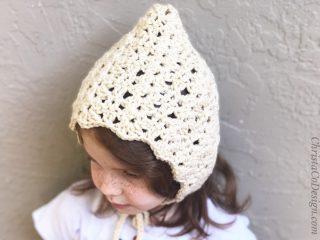 Crochet bonnet pattern in cream yarn on girl.